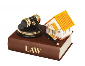 Law book with gavel and model of house.